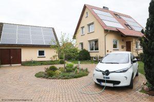 Eine Photovoltaikanlage auf dem Dach, ein Stromspeicher im Keller und ein Elektroauto vor der Tür, geladen mit regenerativer Sonnenenergie